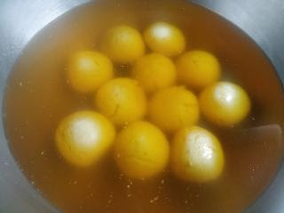 Orange rasgulla in orange color sugar syrup