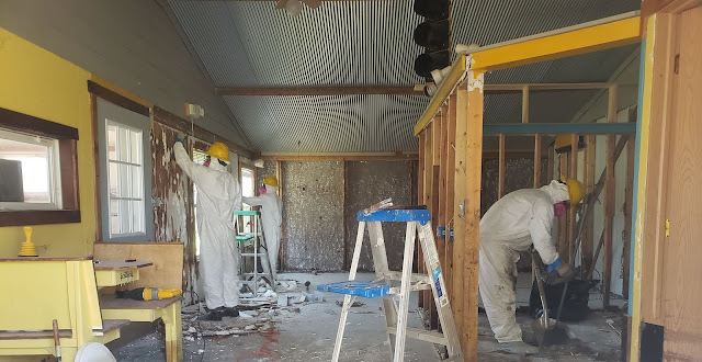 Two AmeriCorps members are wearing full bodied, white, Tyvek protective suits and yellow hard hats while removing water-damaged material from a home.