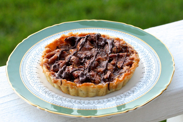 Chocolate Caramel Pecan Tarts on fine china