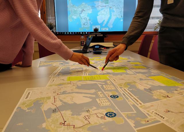 Kuvassa karttoja pöydällä, taustalla tv-näyttö, kahden henkilön käsiä näkyvillä pöydän ympärillä.