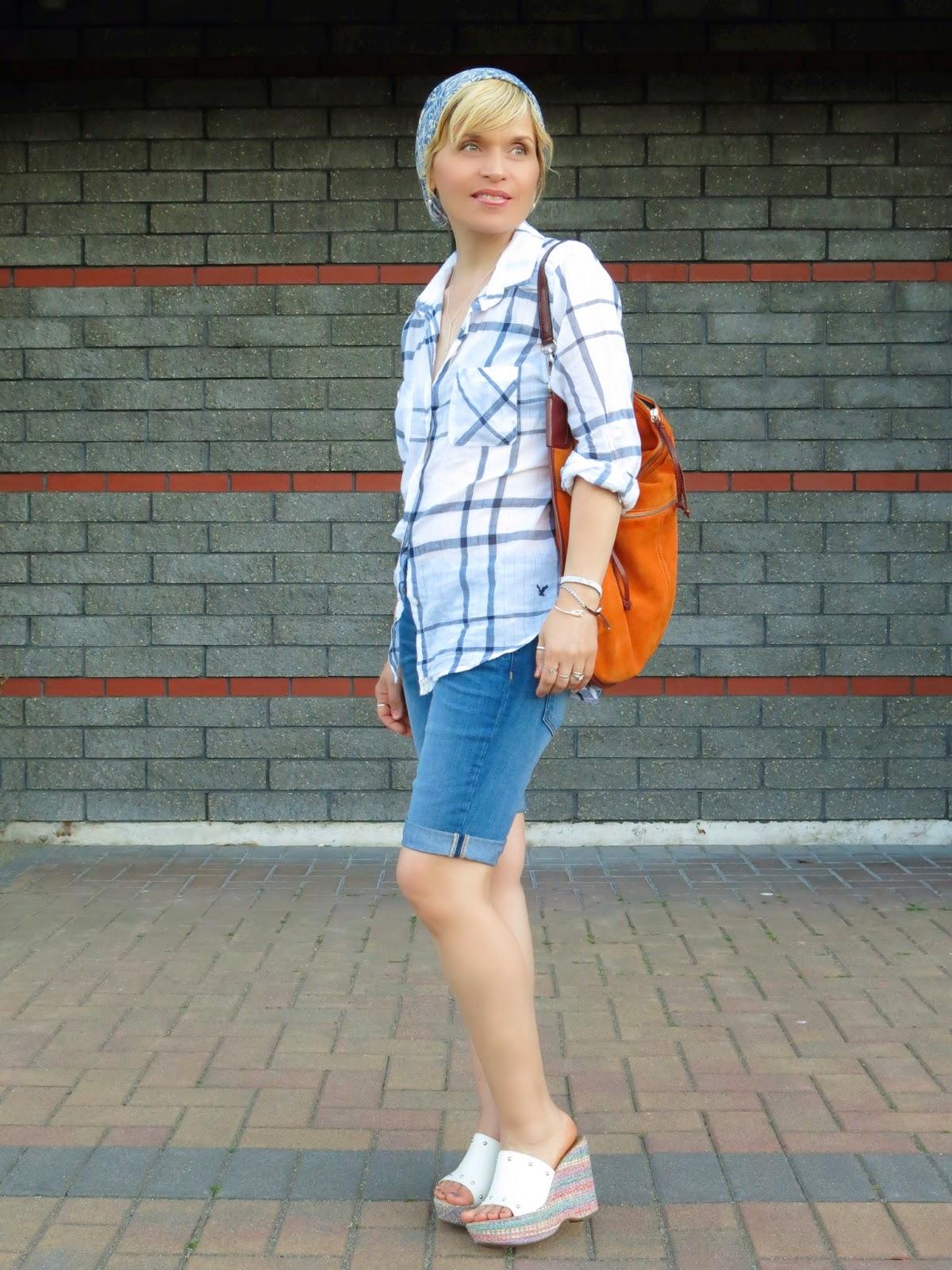 styling a white plaid shirt with denim bermudas, platform mules, and a summer beanie