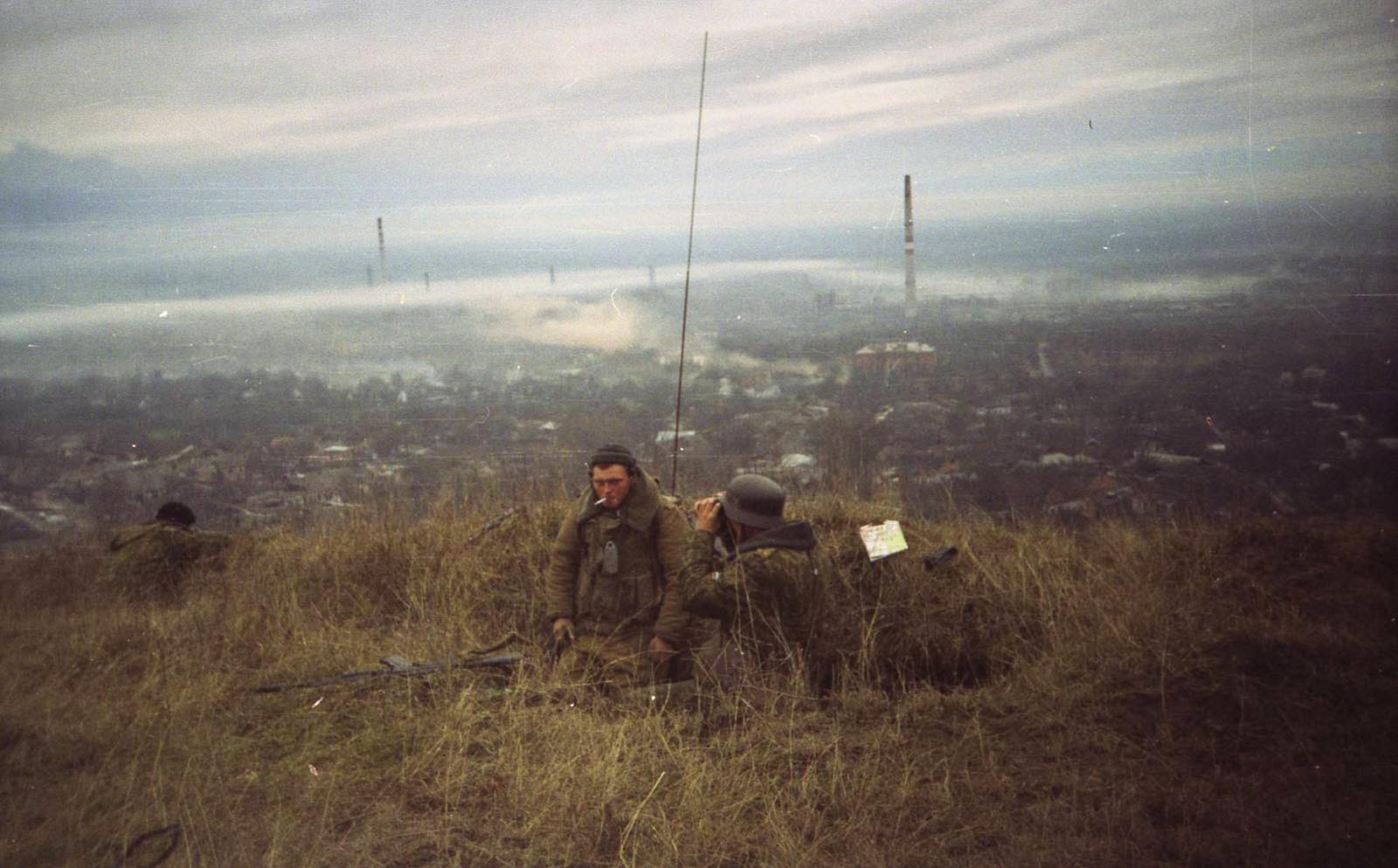 Russian soldiers, one of them wearing a WW2 German helmet, overlooking Grozny, 1999.