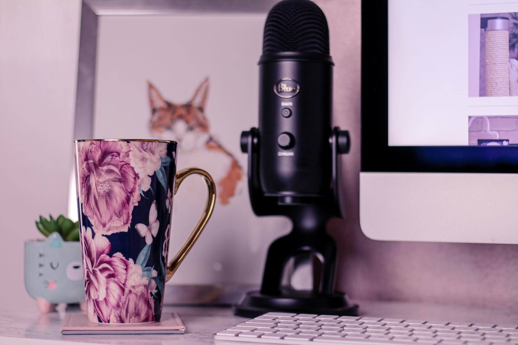 Close up of a flower mug on a white desk with a black blue yetti microphone and cat drawing behind it