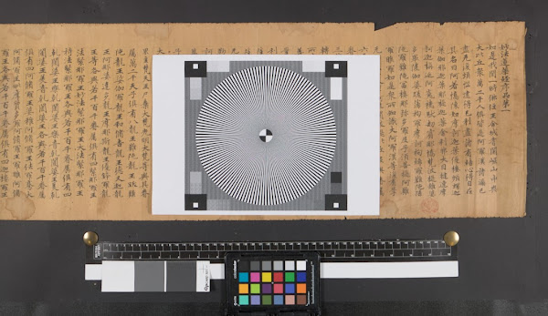 Black background behind a yellowed scroll with Chinese characters on it and a black and white focus target with a multicoloured colour palette and black and white strips at bottom of image.