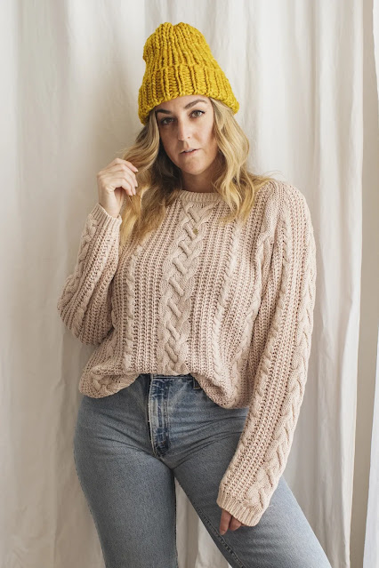 Woman wearing vintage pink cable knit sweater