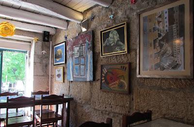 interior de um restaurante com mesas, cadeiras e quadros na parede