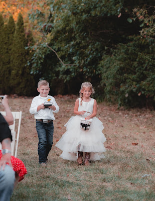 Niña y niño llevando los pétalos y los anillos