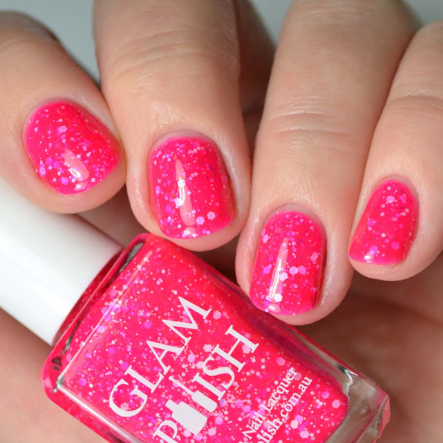 bright pink nail polish with glitter four finger swatch