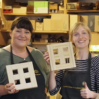 Image of two women proudly showing off their woodworking joints