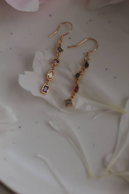 A pair of gold dangling earrings with gemstone pieces.