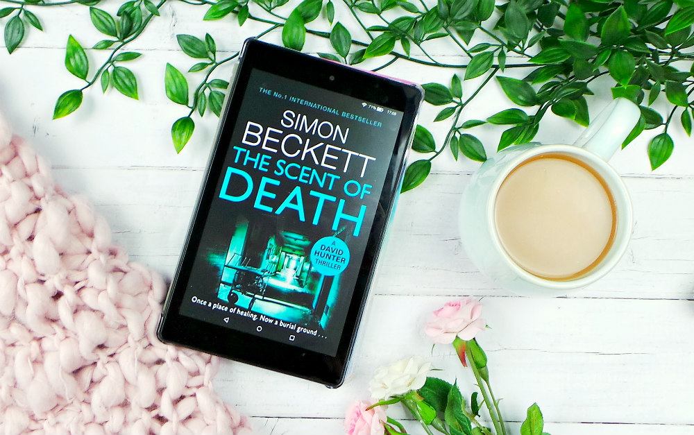 Kindle fire showing the The Scent of Death by Simon Beckett cover. Theres leaves, a pink blanket and roses in the background