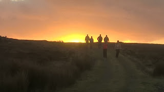 walkers with sunset behind