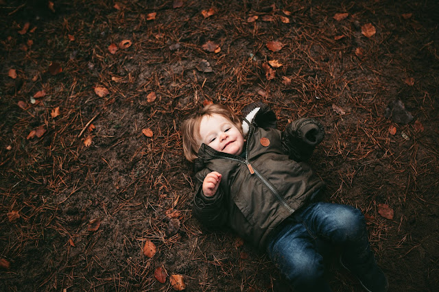 image shows a toddler boy lying on his back in the woods and looking to camera