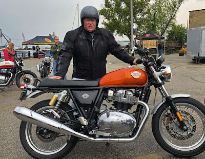 Rider stands with an orange Royal Enfield motorcycle.
