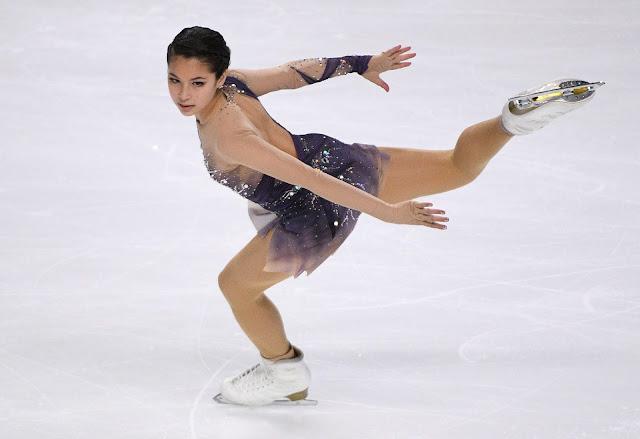 Alysa Liu fazendo giro. A patinadora veste um vestido roxo e está com uma perna flexionada no ar