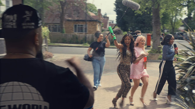 A man looking out of his window, seeing the Spice Girls and a camera crew running towards his door