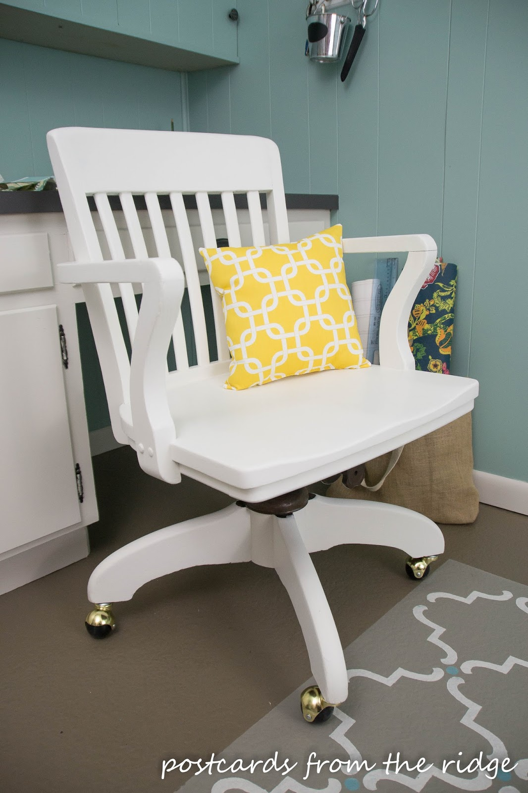 New wheels, a new pillow, and a fresh coat of white dove paint give this wooden swivel office chair a new lease on life.