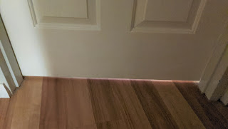 A closed door with light showing through underneath due to 1 inch gap from wooden floors.