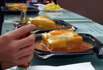 Pratos com sanduiches francesinhas e mão segurando um vidro com pimenta