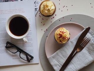 cupcakes on plate sitting next to glasses and coffee