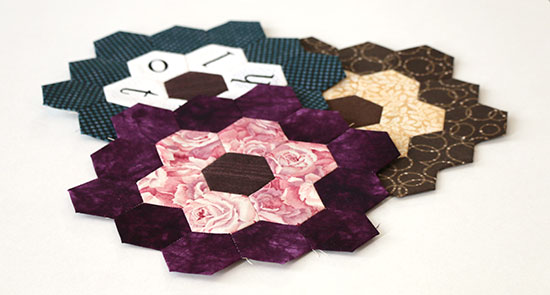 Three overlapping hand sewn hexagon flower blocks in blues, browns, and purples, on a white background.