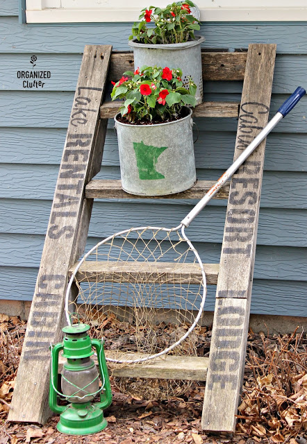 Photo of a ladder stenciled with cabin themed stencils with impatiens planted in minnow buckets