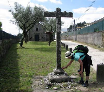 Peregrina de Santiago de Compostela colocando uma pedra em um cruzeiro