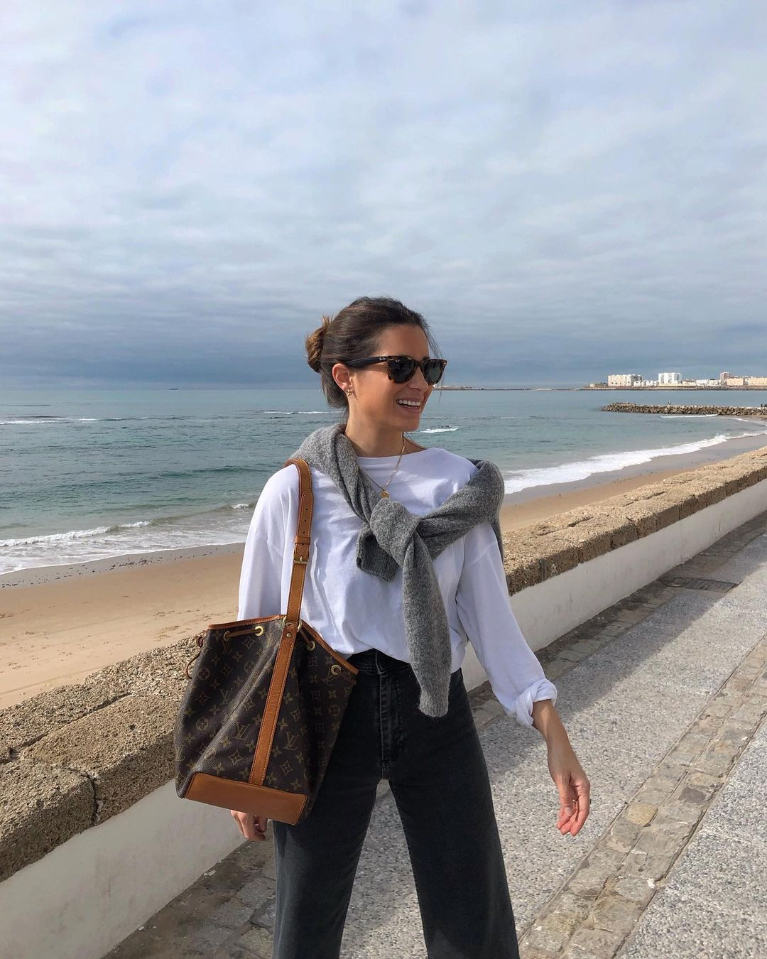 Everyday Casual Spring Outfit Idea from Maria Valdes — White Shirt With a Gray Sweater Over The Shoulders, Ray-Ban Wayfarer Sunglasses, Black Jeans, and Louis Vuitton Bucket Bag