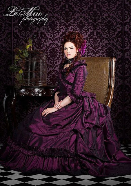 A woman wearing a purple victorian ball gown with a waterfall bustle. A perfect dress for a steampunk masquerade ball.