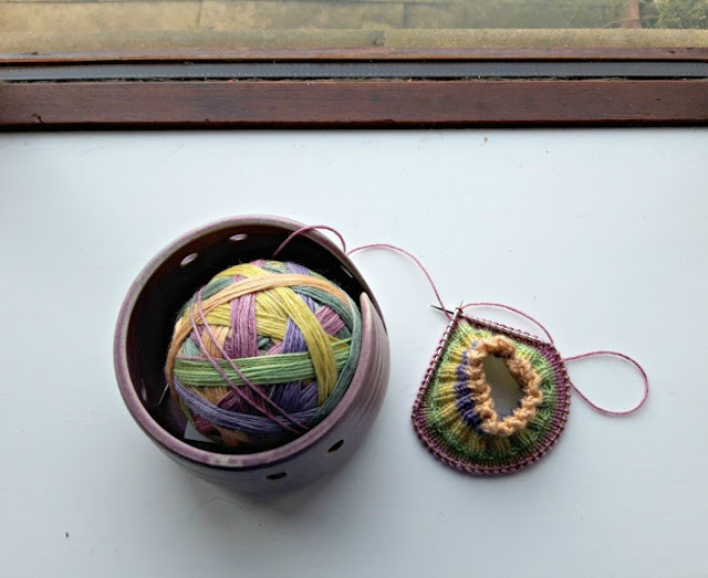 A ball of yarn in a bowl and some knitting on a white window sill