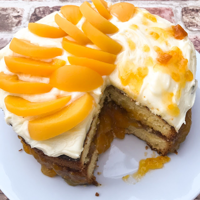 Sponge cake with a jam filling and topped with peaches and jam drizzle