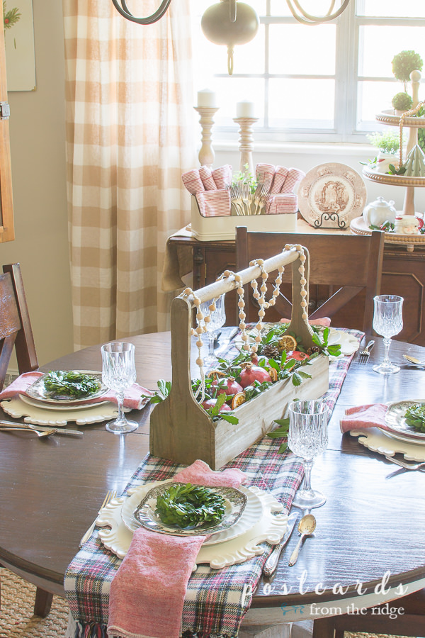 table set with plaid runner, wood caddy centerpiece with pomegranates, crystal glasses, preserved boxwood place setting