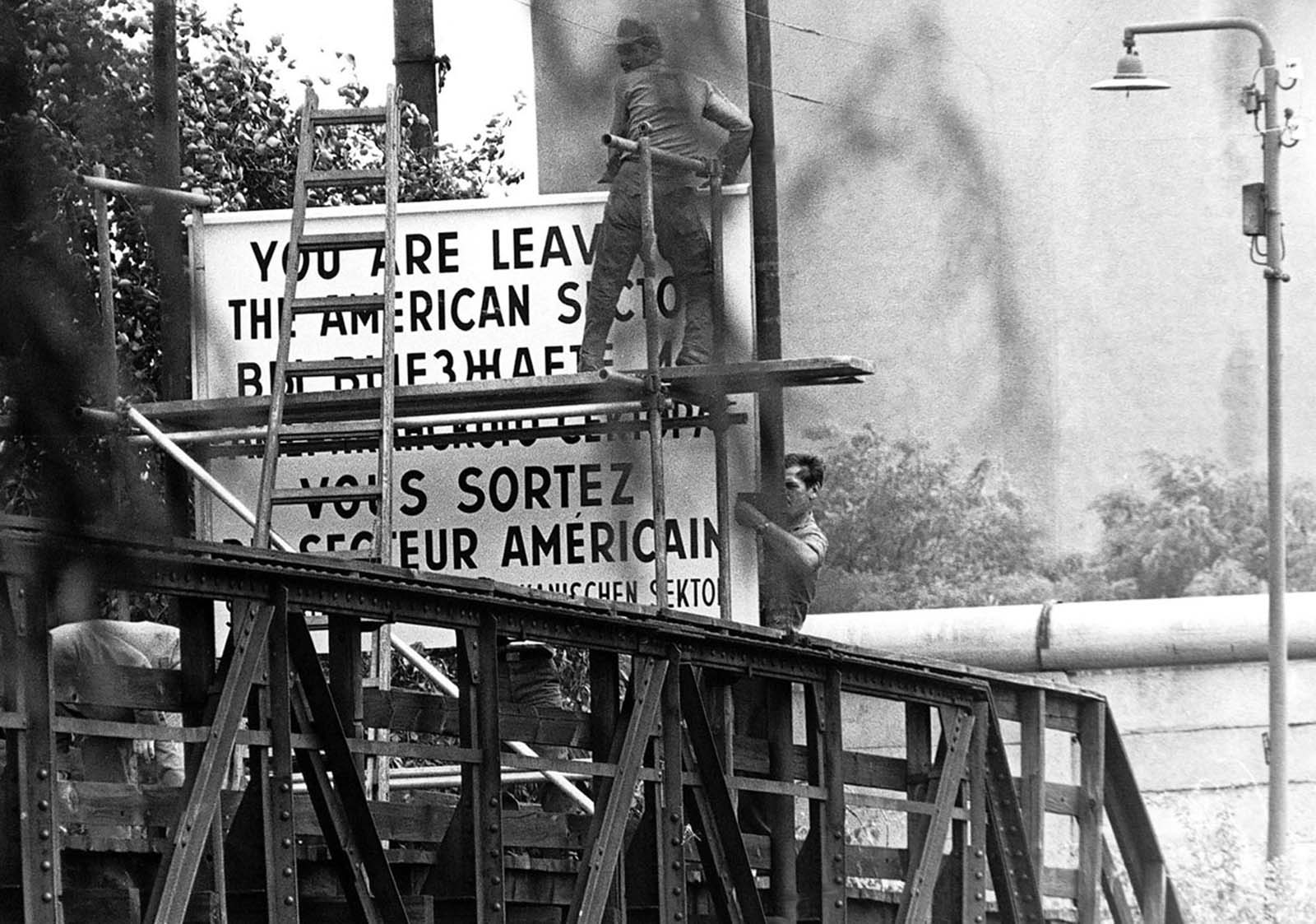 Workers set up a sign warning pedestrians they are leaving the American sector of Berlin, Germany, on Wiener Strasse (Vienna Street) in the district of Kreuzberg in West Berlin, on August 13, 1961. In the background is the Berlin Wall that divides East and West Berlin.