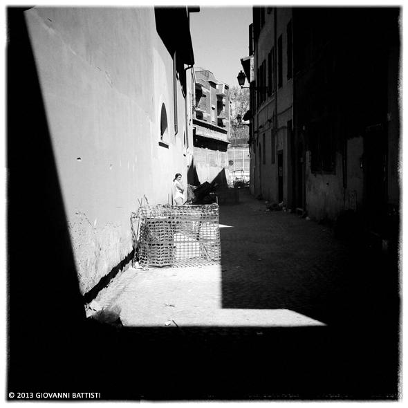 Fotografia in bianco e nero di un vicolo con signora