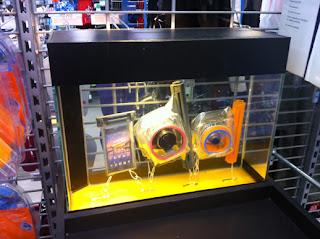 Foto de um aquário na loja com um celular, uma câmera grande profissional e uma câmera pequena, todas dentro da bolsa plástica, no fundo do aquário, seguradas por um fio para não boiar.