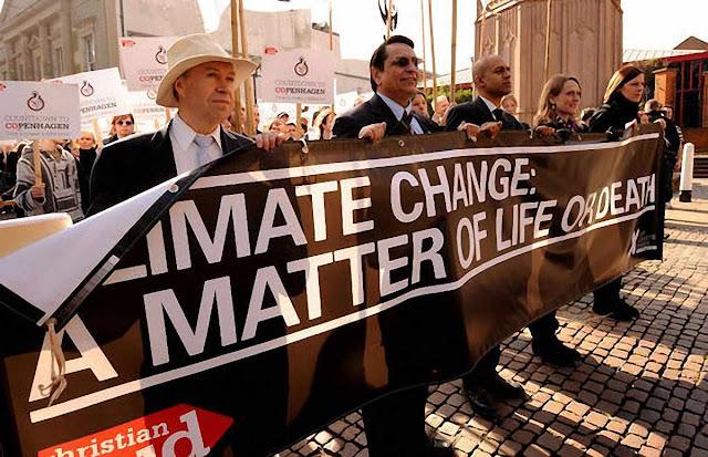 """James Hansen (chapéu) em passeata, Coventry, Inglaterra: """"[O acordo de Paris] é realmente uma fraude, uma falsificação Trata-se de palavras sem valor""""."""