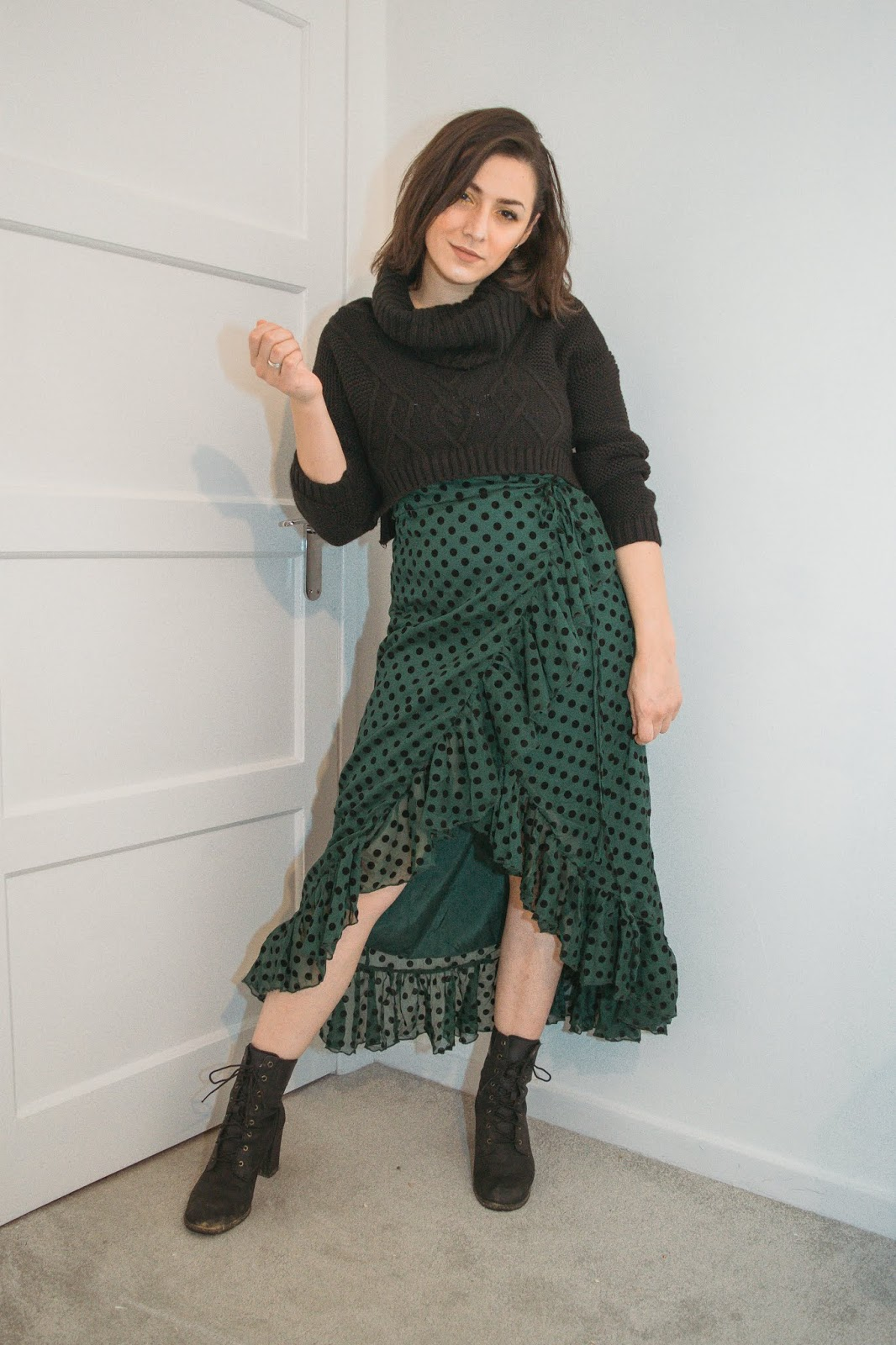 I am standing against a white background wearing a green frill wrap dress with black polka dots that is a mid length. I am wearing a black knitted roll neck jumper over the dress that is cropped from the waist. I am wearing heeled black boots.