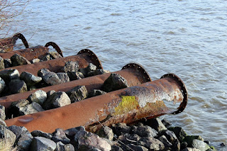 Rusty pipes on a rock bed leading out into water in West Yarmouth, MA