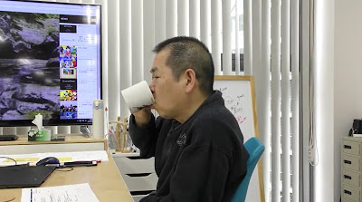 Yu sipping from his mug