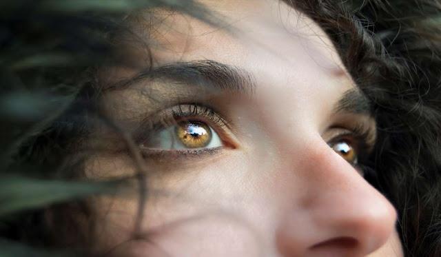 Beautiful woman looking upward with fear in her eyes.
