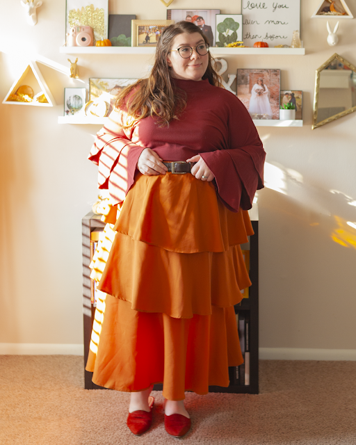 An outfit consisting of a long sleeve burgundy top with three tiers on the sleeves, tucked into an orange three tiered maxi skirt and brown d'orsay flats.