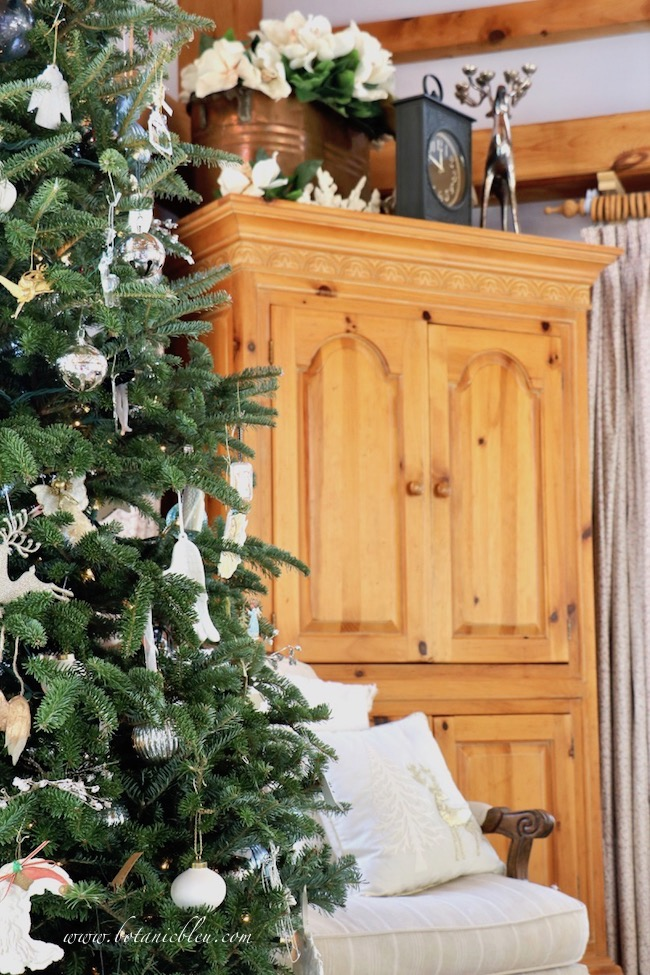French country Christmas living room with Christmas tree and pine armoire
