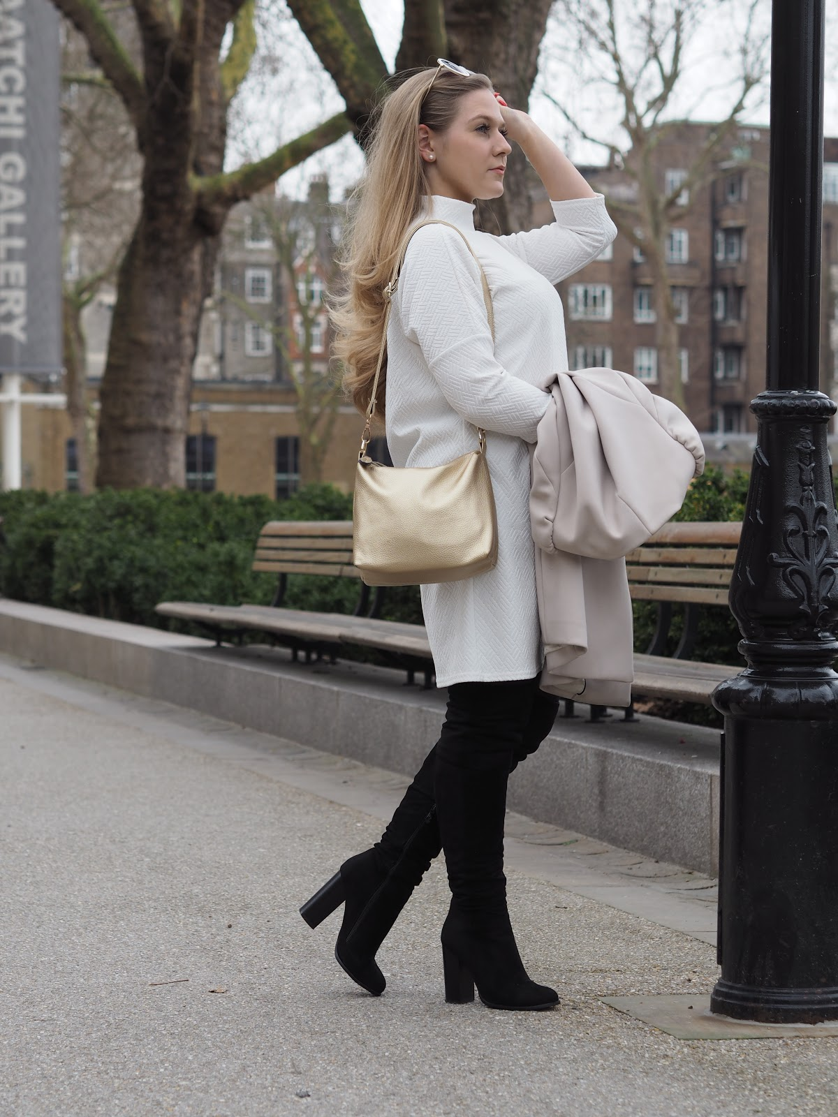 Blonde girl wearing white dress and black thigh high boots in Chelsea, London