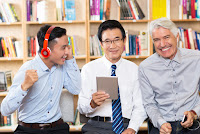 Three adult men-two listening on headphones & one reading on a tablet