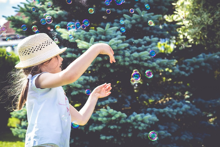 Girl blowing bubbles in the backyard