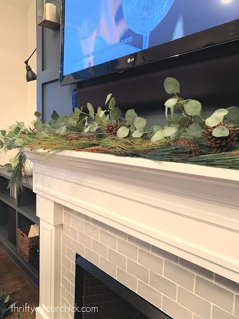 decorating Christmas mantel with greenery