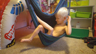 Orion sits in a sky hammock swing chair