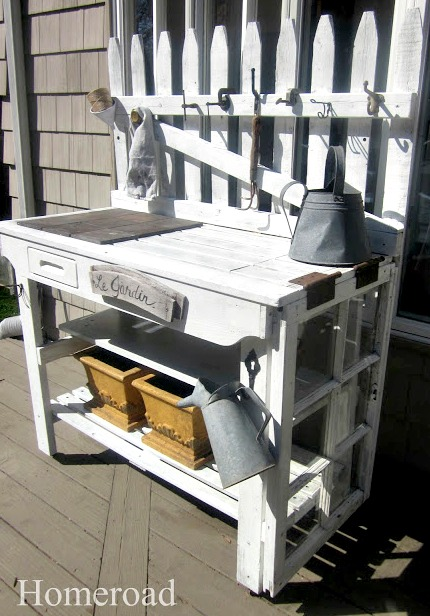 white potting bench with planters and hanging accessiories