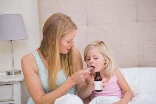 Madre dándole medicina a su hijo.