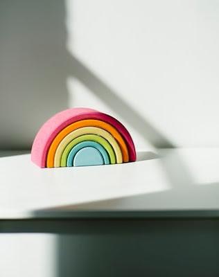 A wooden rainbow display sitting on a shelf